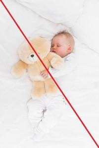 Baby sleeping while holding a teddy bear in a bedroom